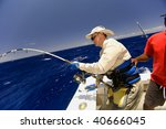 The sailor helps the diligent fisher to take out huge fish - stock photo