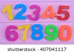 numbers on purple wooden table | Shutterstock . vector #407041117