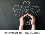Small photo of hands protects a house from the elements - rain or storm