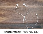 white earphones on wooden... | Shutterstock . vector #407702137
