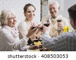 Small photo of Mature and young married couples toasting, sitting beside table, drinking red wine