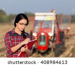 Young Woman Farmer Standing On...