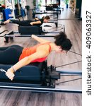 Small photo of Woman doing back and arms exercises using a reformer bed