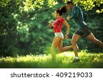 young couple jogging at the... | Shutterstock . vector #409219033