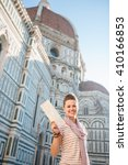 Small photo of An amble around awe-inspiring Duomo in Florence, Italy. Happy woman tourist showing map while standing in the front of Duomo