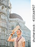 Small photo of An amble around awe-inspiring Duomo in Florence, Italy. Smiling woman tourist with map sightseeing in Florence