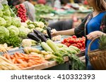 Young Woman Buying Vegetable O...