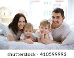 happy family lying in bed on... | Shutterstock . vector #410599993
