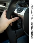 Small photo of Closeup photo of female driver adjusting cruise control system on steering wheel