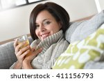 Small photo of 40-year-old woman relaxing in sofa with cup of tea