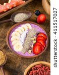 Small photo of Acai berry smoothie bowl topped with chia seeds, coconut flakes, banana, strawberries and kiwi with variety of superfoods on rustic wooden table. Healthy breakfast. Selective focus