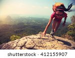 Stock photo young asian woman hiker climbing rock on mountain peak cliff 412155907