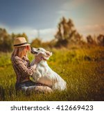 Stock photo girl with her best friend the dog is resting and playing in the park 412669423
