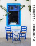 Blue Table And Chairs In Front...