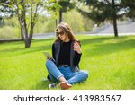 girl sitting on the grass with... | Shutterstock . vector #413983567