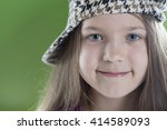 Small photo of smiling girl in checkered acock hat