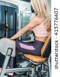 Small photo of Adduction or abductor machine - Attractive girl exercising her thighs in the gym
