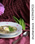 Small photo of Green Russian traditional soup shchi served with sliced boiled eggs, fresh parsley and sorrel leaves in porcelain plate, vintage spoon on the burgundy textile tablecloth background, vertical