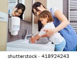 Kid Washing Hands With Mom In...