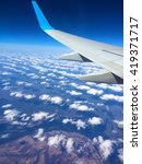 Small photo of Aircraft wing and clouds, Wing aircraft in altitude during flight, Aircraft wing flying over clouds, Aircraft wing on cloudscape and blue sky, Aircraft wing on the clouds, flying background, window