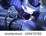 Worker Welding Metal Piping...