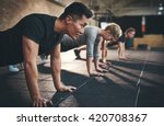 Stock photo fit young people doing pushups in a gym looking focused 420708367