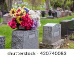 Flowers On A Tombstone In A...