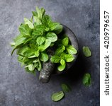 Small photo of Fresh mint leaves in mortar on stone table. Top view