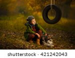 Stock photo stylish fashionable young boy playing with husky puppy dog in the woods near wheel swing autumn 421242043