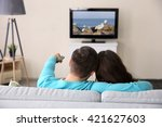 young couple watching tv on a... | Shutterstock . vector #421627603