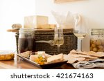 Small photo of Two glasses of wine with servings of cheese and biscuits alongside a jar of honer, olives, and a wicker basket.