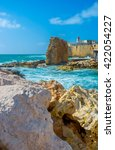 Small photo of The rocky shore in place of the former Crusaders' harbor of Acre, Israel.