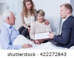 Small photo of Shot of a family listening to a young man holding a last will form
