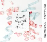 Stock photo quote do small things with great love written in calligraphy style on paper with pink petals and 422494303