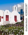 Small photo of Classical Greek church in the garden with flowers