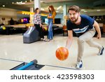Handsome Man Throwing Bowling...