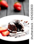 Small photo of Chocolate fondant with strawberry on black wooden table
