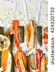 Small photo of Roasted winter vegetables on aluminum foil on tray,pepper, zucchini, carrot, celery, tomato. Top view.
