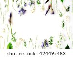 floral frame with purple iris flower, lily of the valley, branches, leaves and petals isolated on white background. flat lay, overhead view