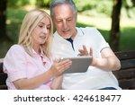 mature couple using a digital... | Shutterstock . vector #424618477