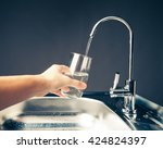 hand pouring a glass of water... | Shutterstock . vector #424824397