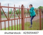 Boy Climbs Up A High Fence....