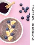 Small photo of Acai berry smoothie bowl with banana, blueberry and chia seeds. Pink background. Top view