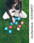 Small photo of NOVI SAD, SERBIA- MAY 17, 2016: Young woman sitting on the grass with tablet - Facebook, Gmail, Instagram, Wikipedia, YouTube and other application icons. Editorial Use Only
