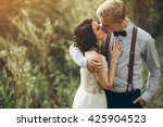bride and groom kissing in the... | Shutterstock . vector #425904523