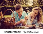 loving couple eating grapes on... | Shutterstock . vector #426052363