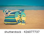 flip flops and bag on sandy... | Shutterstock . vector #426077737