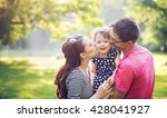 happy family hugging in a park | Shutterstock . vector #428041927