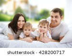 happy family lying in bed on... | Shutterstock . vector #428200717