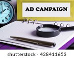 Small photo of Ad Campaign - Yellow Office Folder on Background of Working Table with Magnifying glass, a pen and clock -business and finance concept
